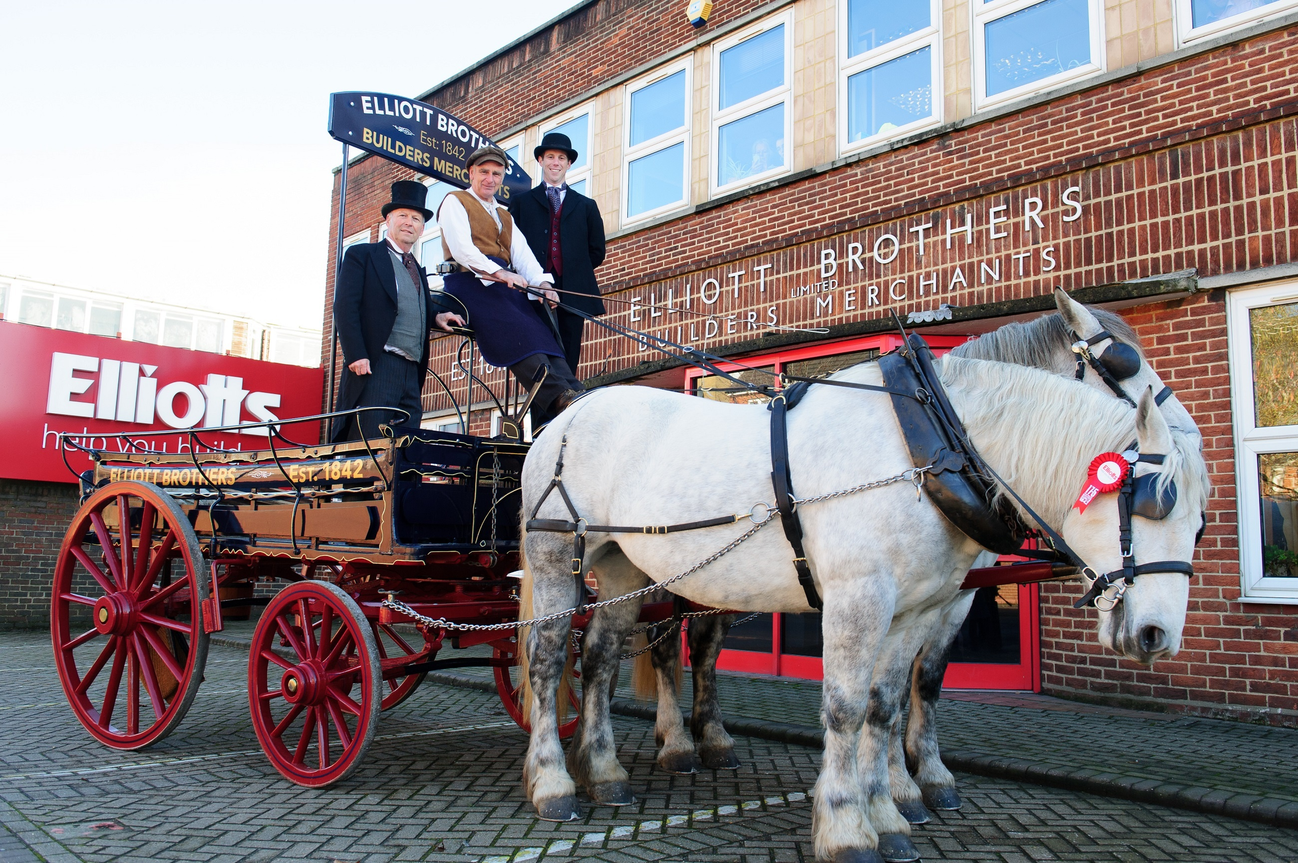 Stuart Mason-Elliott and Tom Elliott with the horse and cart outside head office
